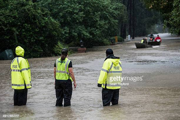 Police watch rescue boats looking for trapped in their homes October 4 2015 in Columbia South Carolina South Carolina experienced a record rainfall...