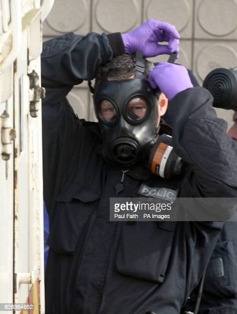 Police wearing Gas masks return to the Alexander bar in North Belfast Friday 3 March 2006 Seventeen men were arrested following a police search of a...