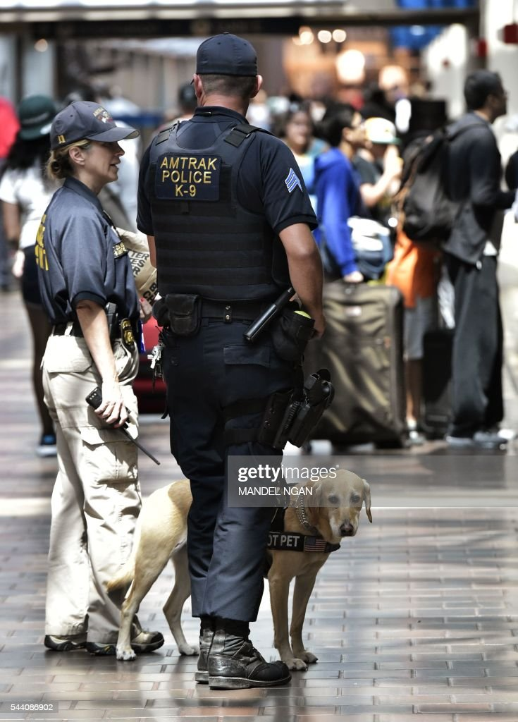 Police with a dog patrol inside of Union Station on July 1, 2016, ahead of the Independence Day holiday weekend, in Washington, DC. / AFP / Mandel Ngan