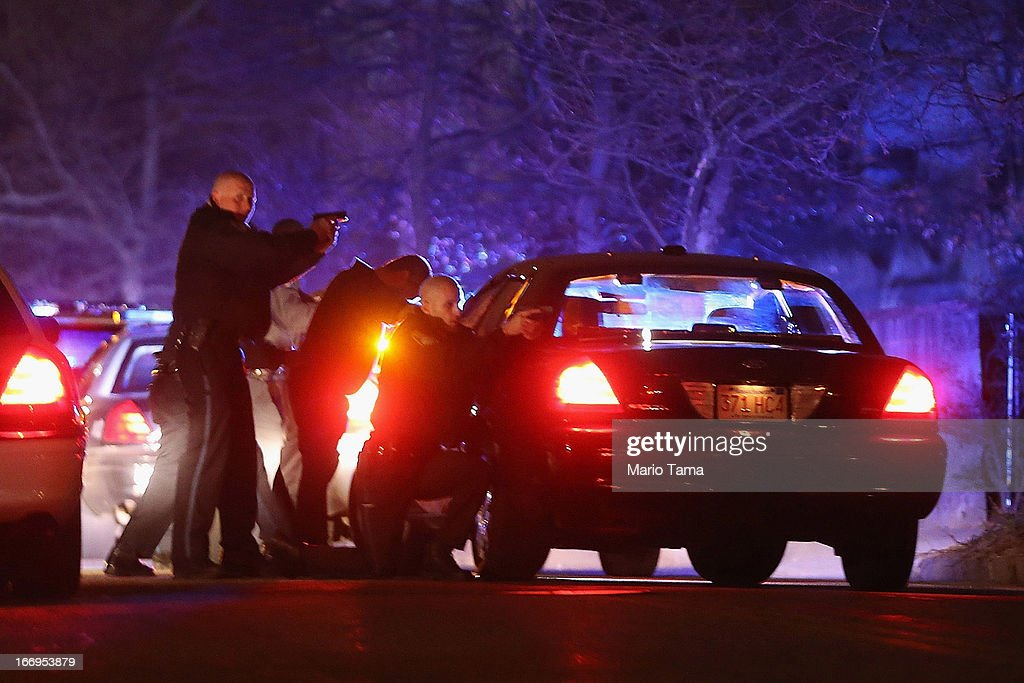 Police with guns drawn search for a suspect on April 19, 2013 in Watertown, Massachusetts. Earlier, a Massachusetts Institute of Technology campus police officer was shot and killed late Thursday night at the school's campus in Cambridge. A short time later, police reported exchanging gunfire with alleged carjackers in Watertown, a city near Cambridge. It's not clear whether the shootings are related or whether either are related to the Boston Marathon bombing.