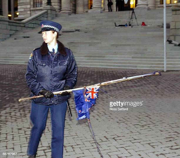 A police woman holds the remnants of New Zealand flags which were burnt on the forecourt of Parliament Wellington New Zealand Thursday July 29 2004...