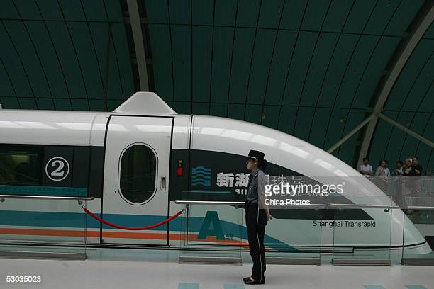 A police woman stands beside a Maglev train also known as the magnetic levitation train at a station on June 7 2005 in Shanghai China Shanghai boasts...