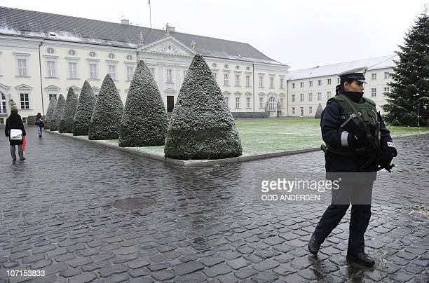A police woman wearing a bullet proof vest an holding a machine gun patrols in front of in front of the Bellevue Palace after German President...