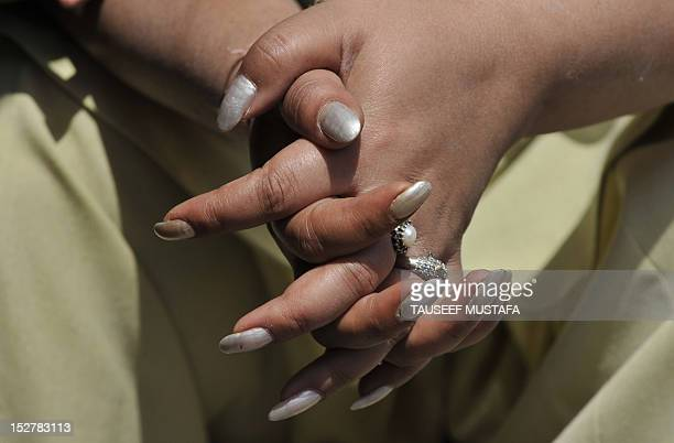 A police woman's hands are pictured as she takes a break during a protest by nursing students against their exam results in Srinagar on September 26...