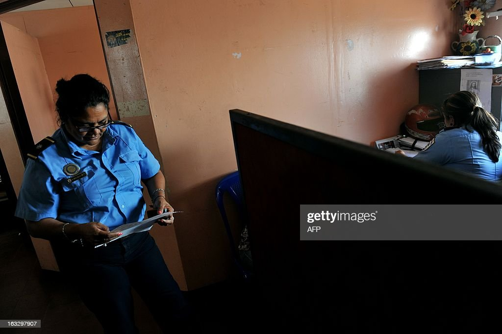 Police women at the Women's Commissioner office, District 3, in Managua, on March 7, 2013, after filing a complaint against her former boyfriend, who attempted to force her to return with him, for psychological abuse. In Nicaragua in 2012 85 women were murdered and there were over 32,000 complaints of domestic violence and sexual abuse. AFP PHOTO/Hector RETAMAL