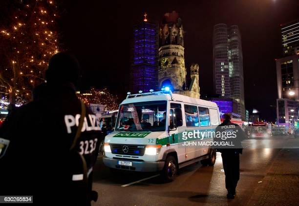 A policecar stands at the site where a truck crashed into a christmas market at Gedächtniskirche church in Berlin on December 19 2016 killing at...