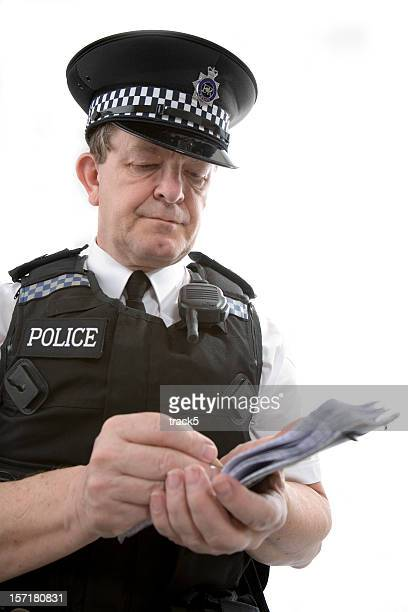 UK policeman: a uniformed officer taking notes from a case