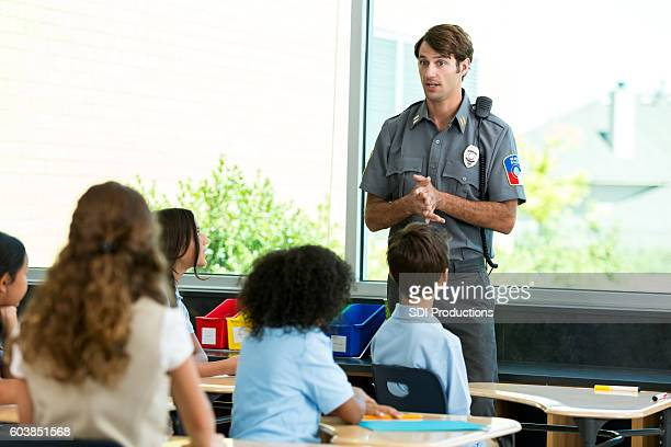 Policeman addresses a classroom of private school students