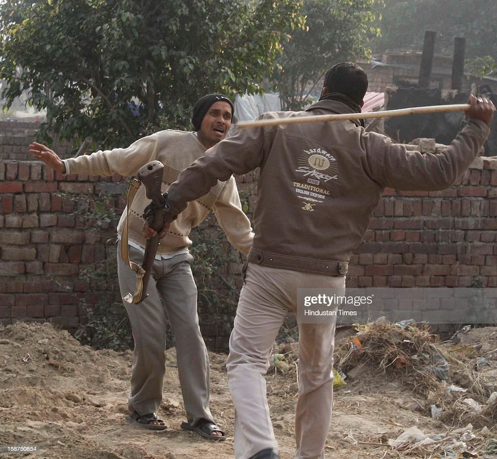 A policeman aims to beat a bystander during the protest by students in support of rape victim at Sector 49 on December 27, 2012 in Noida, India. Huge traffic jam was witnessed and agitated mob ransacked some vehicles after which police had to Lathi charge to bring situation back to normal.
