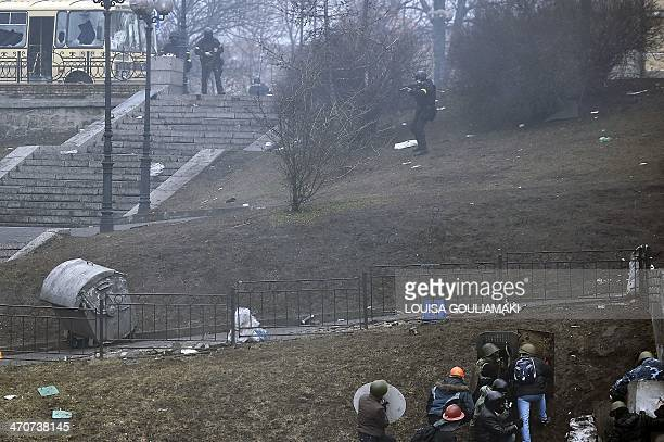 A policeman aims towards protesters in central Kiev on February 20 2014 Hundreds of armed protesters charged police barricades Thursday on Kiev's...
