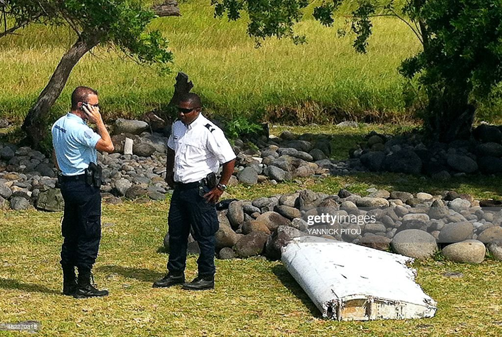 A policeman and a gendarme stand next to a piece of debris from an unidentified aircraft found in the coastal area of Saint-Andre de la Reunion, in the east of the French Indian Ocean island of La Reunion, on July 29, 2015. The two-metre-long debris, which appears to be a piece of a wing, was found by employees of an association cleaning the area and handed over to the air transport brigade of the French gendarmerie (BGTA), who have opened an investigation. An air safety expert did not exclude it could be a part of the Malaysia Airlines flight MH370, which went missing in the Indian Ocean on March 8, 2014. AFP PHOTO / YANNICK PITOU