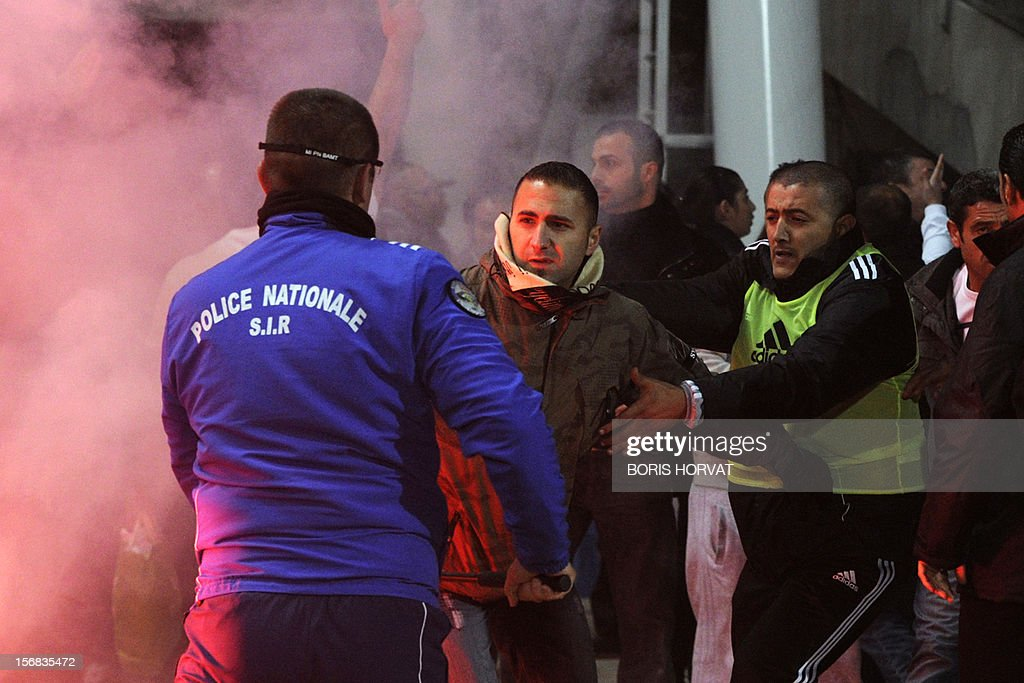 A policeman and a stadium's security employee stops a Fenerbahce's fan (C) during the UEFA Europa League Group C3 football match between Olympique de Marseille and Fenerbahce SK, on November 22, 2012, at the velodrome stadium in Marseille. AFP PHOTO / BORIS HORVAT