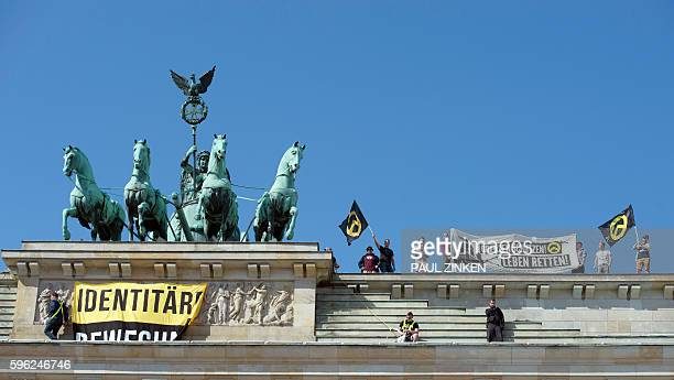A policeman and activists of the 'Identitarian Movement' stand next to the Quadriga sculpture ontop of Berlin's landmark the Brandenburg Gate as the...