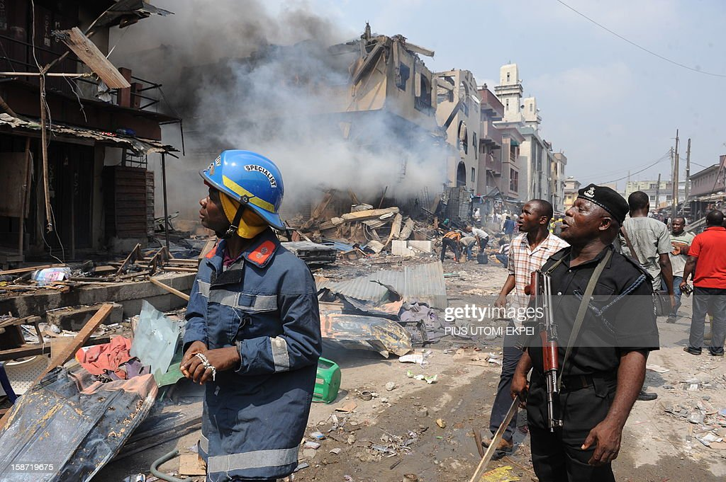 A policeman and firefighter look at building stocked with fireworks on fire in Lagos on December 26, 2012. Fire ripped through a crowded neighbourhood in Nigeria's largest city and wounded at least 30 people after a huge explosion rocked a building believed to be storing fireworks, officials said. AFP PHOTO/PIUS UTOMI EKPEI