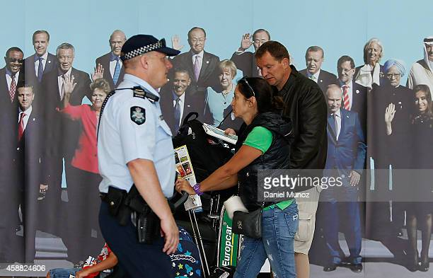 Policeman and passengers walk past a banner with the G20 leaders at Brisbane airport on November 12 2014 in Brisbane Australia World economic leaders...