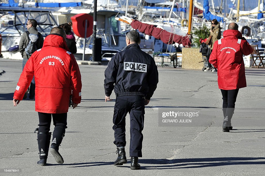 A policeman and rescuers walk near the harbour on October 29, 2012 as they take part in the search for a 12-year-old British boy, who disappeared on October 27, on Porquerolles island, southeastern France. Sixty soldiers and three civil security dog-handlers from Brignoles are paricipating in the search.