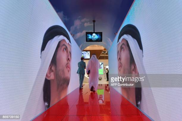 A policeman and visitor walk through a security tunnel at the Gitex 2017 exhibition at the Dubai World Trade Center in Dubai on October 10 2017...