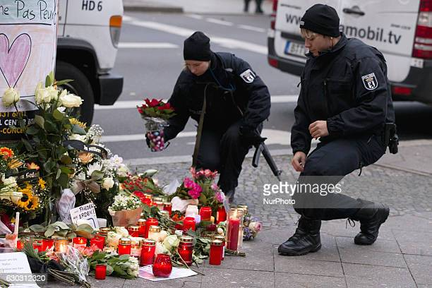 A policeman and woman lay flowers and a candle on the ground in a makeshift memorial close to the KaiserWilhelmGedaechtniskirche in Berlin Germany on...