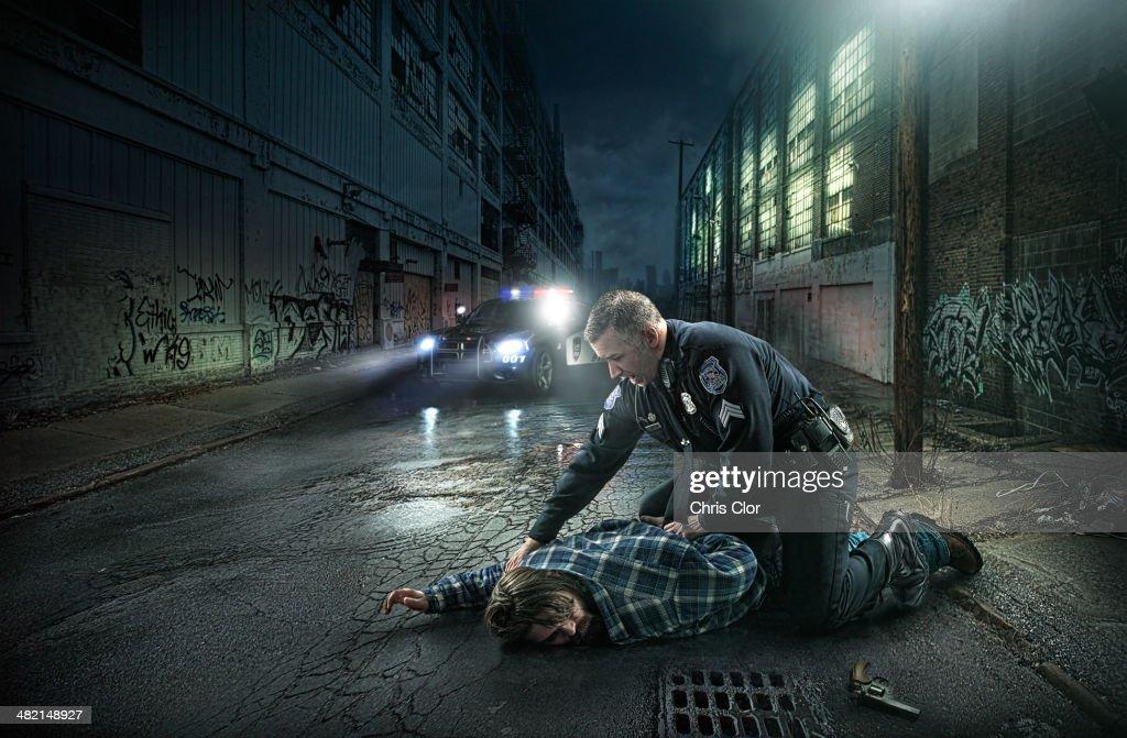 Policeman arresting man on city street : Stock Photo