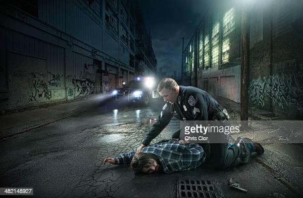 Policeman arresting man on city street