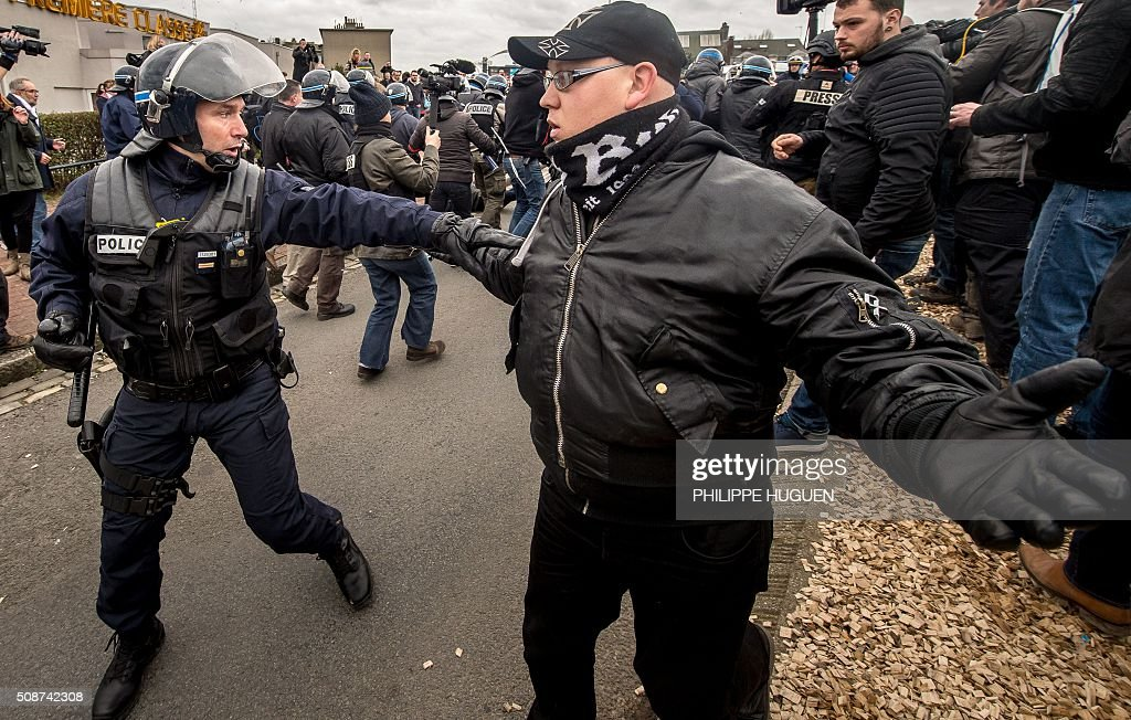 A policeman arrests a supporter of the Pegida movement (Patriotic Europeans Against the Islamisation of the Occident) during a demonstration in Calais, northern France on February 6, 2016. Anti-migrant protesters in the French port city of Calais clashed with police as they defied a ban and rallied in support of a Europe-wide initiative by the Islamophobic Pegida movement. / AFP / PHILIPPE HUGUEN