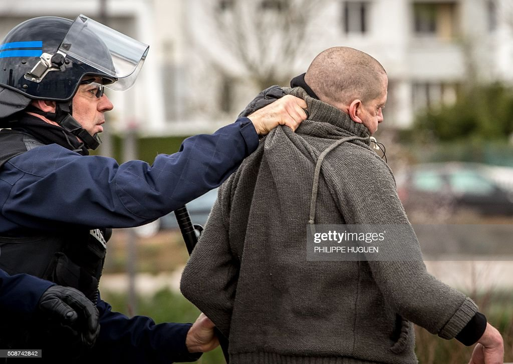 A policeman arrests supporters of the Pegida movement (Patriotic Europeans Against the Islamisation of the Occident) during a demonstration in Calais, northern France on February 6, 2016. Anti-migrant protesters in the French port city of Calais clashed with police as they defied a ban and rallied in support of a Europe-wide initiative by the Islamophobic Pegida movement. / AFP / PHILIPPE HUGUEN