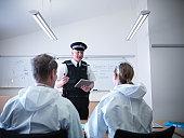 Policeman briefing forensic scientists