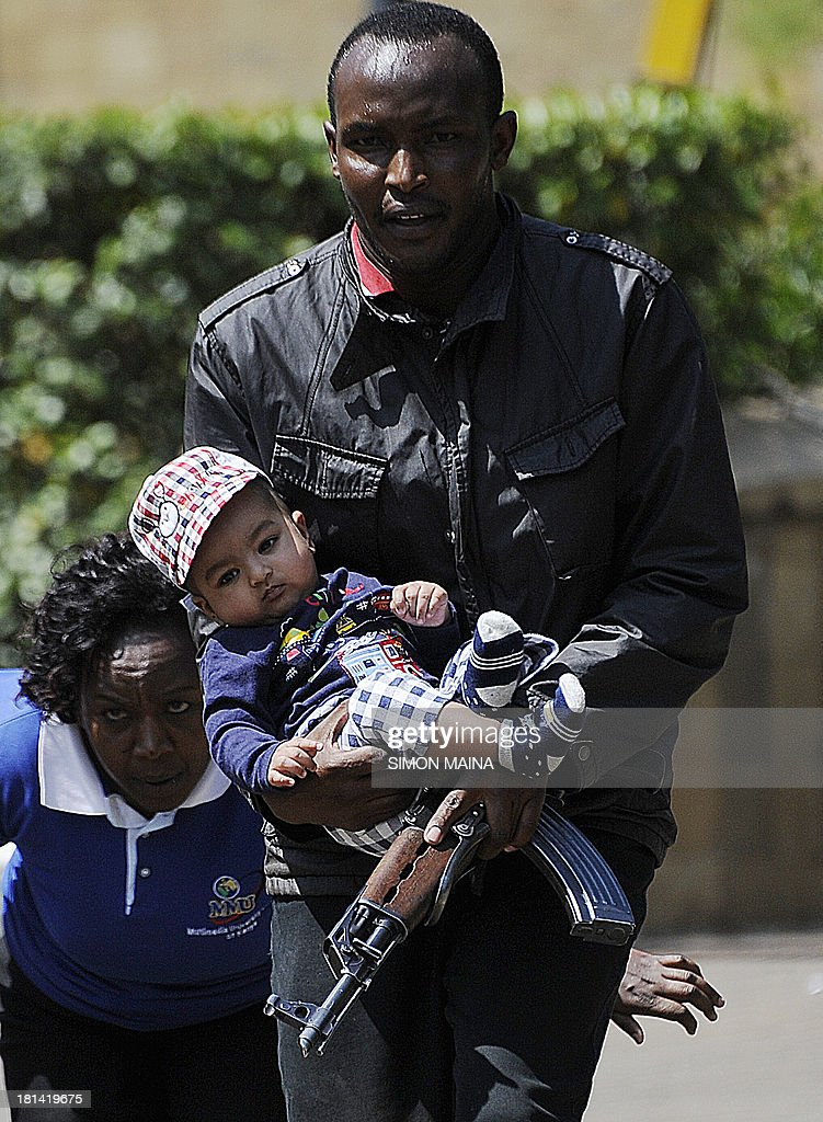A policeman carries a baby to safety after masked gunmen stormed an upmarket mall and sprayed gunfire on shoppers and staff, killing at least six on September 21, 2013 in Nairobi. The Gunmen have taken at least seven hostages, police and security guards told an AFP reporter at the scene.