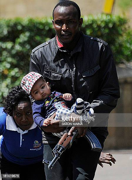 A policeman carries a baby to safety after masked gunmen stormed an upmarket mall and sprayed gunfire on shoppers and staff killing at least six on...