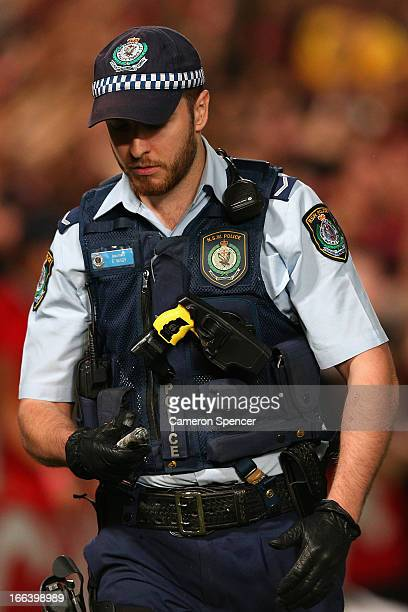 A policeman carries a flare during the ALeague Semi Final match between the Western Sydney Wanderers and the Brisbane Roar at Parramatta Stadium on...