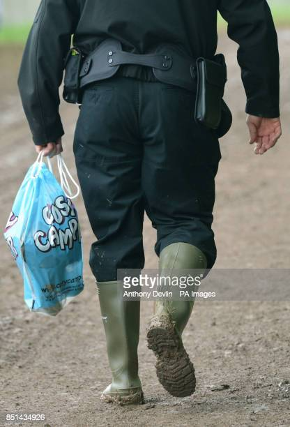 A policeman carries a packet of toilet paper during the first performance day of the Glastonbury 2013 Festival of Contemporary Performing Arts at...