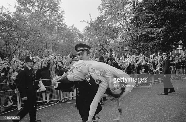 A policeman carries away a fan injured in the crush after members of The Osmonds pop group appeared on the balcony of a hotel in Belgravia London...