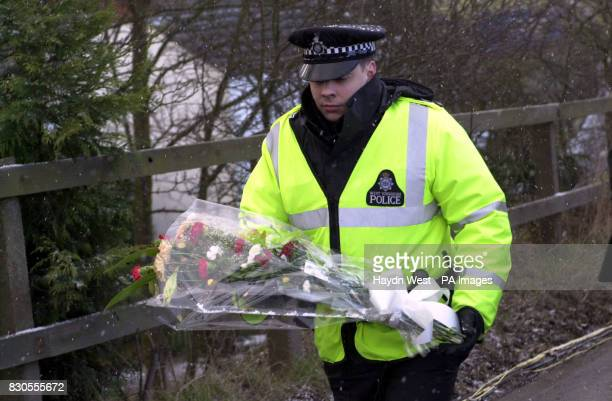 A policeman carries flowers to be laid down on the bridge above the wreckage at Great Heck North Yorkshire Thirteen people died after a GNER express...