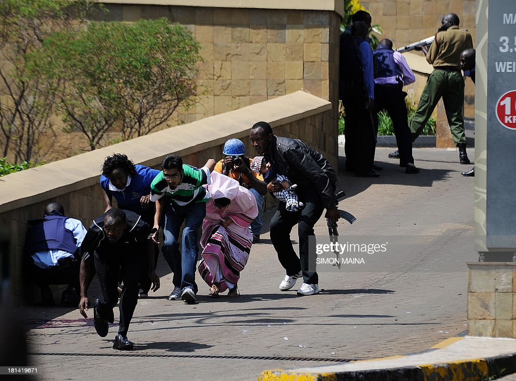 A policeman carry's a baby to safety after masked gunmen stormed an upmarket mall and sprayed gunfire on shoppers and staff, killing at least six on September 21, 2013 in Nairobi. The Gunmen have taken at least seven hostages, police and security guards told an AFP reporter at the scene.