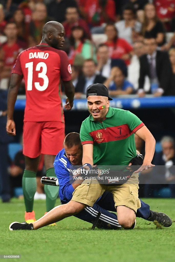 A policeman catches a Portugal supporter after he invaded the pitch during the Euro 2016 quarter-final football match between Poland and Portugal at the Stade Velodrome in Marseille on June 30, 2016. / AFP / ANNE