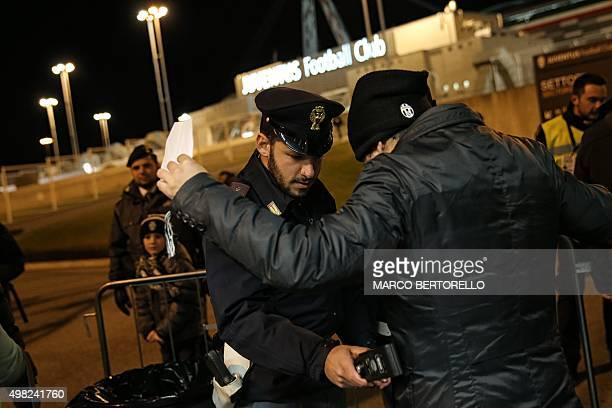 A policeman checks supporters with a metal detector at the entrance of the Juventus stadium before the Italian Serie A football match Juventus Vs AC...