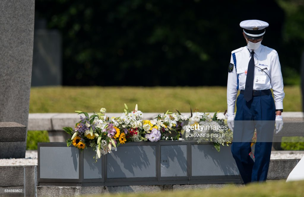 A policeman checks the flowers at the cenotaph at the Hiroshima Peace Memorial in Hiroshima on May 27, 2017. US President Barack Obama was to make history later on May 27 when he travels to Hiroshima -- becoming the first sitting US leader to visit the site that ushered in the age of nuclear conflict. / AFP / JOHANNES