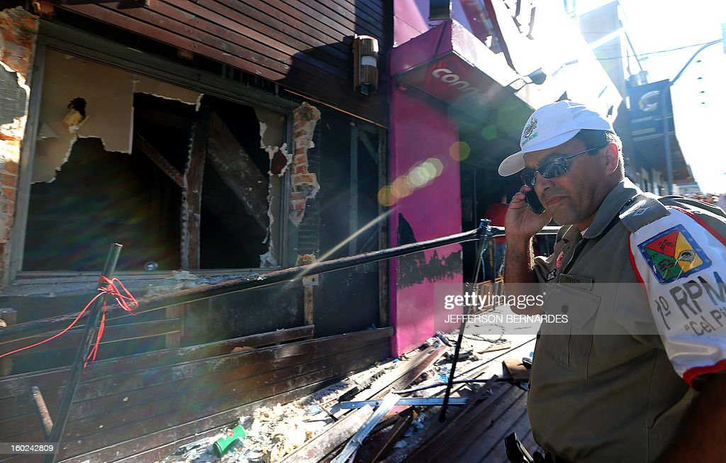 A policeman checks the Kiss nightclub where a blaze on the eve killed more than 230 people, on January 28, 2013 in Santa Maria, southern Brazil. Brazilian police arrested four suspects --two of the Kiss club's owners, along with a pair of musicians who starred in the ill-fated pyrotechnic show, in the wake of the nightclub fire that forced sports officials to defend preparations for the World Cup and Olympics. AFP PHOTO / JEFFERSON BERNARDES