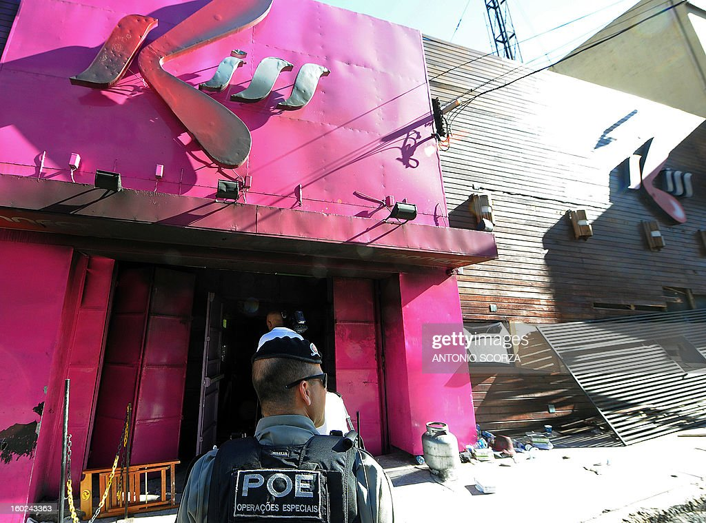 A policeman checks the Kiss nightclub where a blaze on the eve killed more than 230 people, on January 28, 2013, in Santa Maria, southern Brazil. Brazilian police arrested four suspects --two of the Kiss club's owners, along with a pair of musicians who starred in the ill-fated pyrotechnic show, in the wake of the nightclub fire that forced sports officials to defend preparations for the World Cup and Olympics.. AFP PHOTO ANTONIO