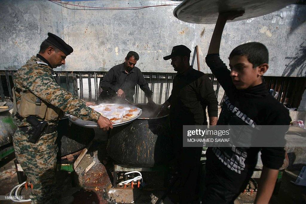 A policeman collects food for himself and colleagues who are on duty guarding pilgrims taking part in the Arbaeen religious festival which marks the 40th day after Ashura commemorating the seventh century killing of Prophet Mohammed's grandson, Imam Hussein, in the shrine city of Karbala, southwest of Iraq's capital Baghdad, on January 1, 2013.