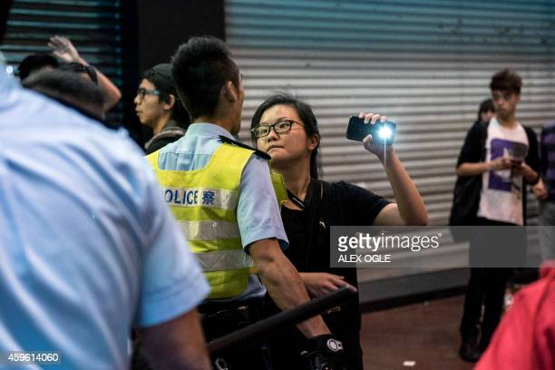 A policeman confronts a woman and tries to stop her from filming other officers as they restrain a prodemocracy protester in the Mongkok district of...