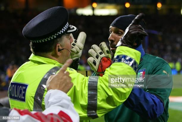 A policeman confronts Italy goalkeeper Gianluigi Buffon