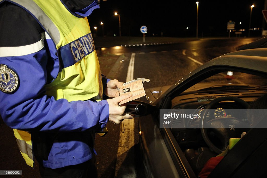 A policeman controls the license of a driver during the New Year's night on January 1, 2013 in Breteville-sur-Odon, near the northwestern city of Caen.