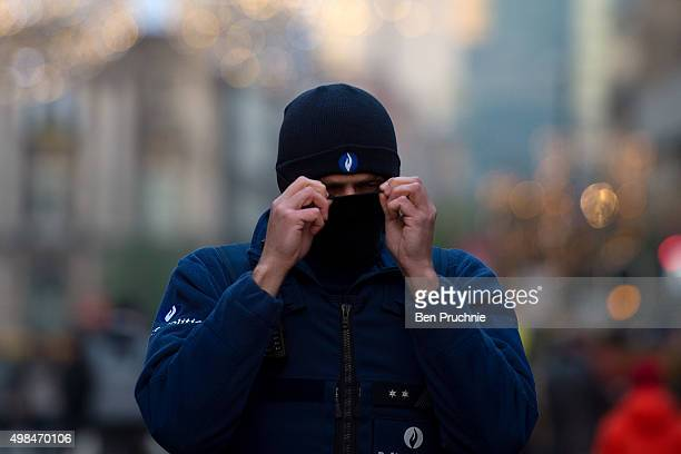 A policeman covers his face with a balaclava on Boulevard Anspach on November 23 2015 in Brussels Belgium Security has been tightened in the nation's...