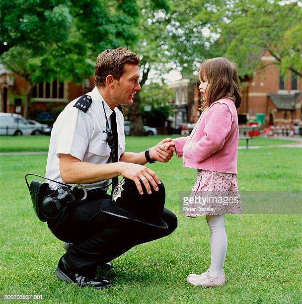 Policeman crouching to talk girl (3-5), outdoors, side view