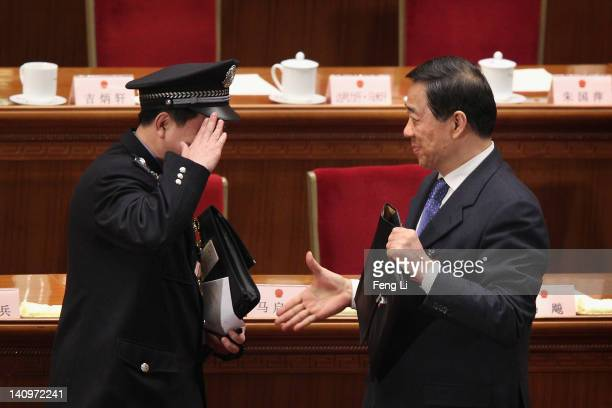A policeman delegate salute to China's Chongqing Municipality Communist Party Secretary Bo Xilai after the third plenary meeting of the National...