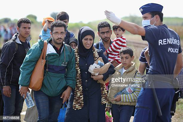 A policeman directs migrants to a holding area for food and water after crossing the border from Serbia into Hungary along the railway tracks close...