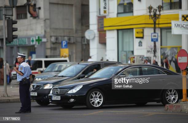 A policeman directs traffic as a Mercedes drives by in the city center on September 6 2013 in Bucharest Romania While the country's economic output...