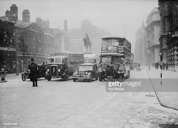 A policeman directs traffic on a snowy day in Whitehall London 19th December 1938