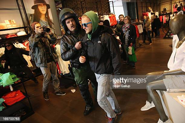 A policeman dressed in riot gear evicts a Blockupy protester from a clothing store in the Zeil pedestrian shopping street on May 31 2013 in Frankfurt...